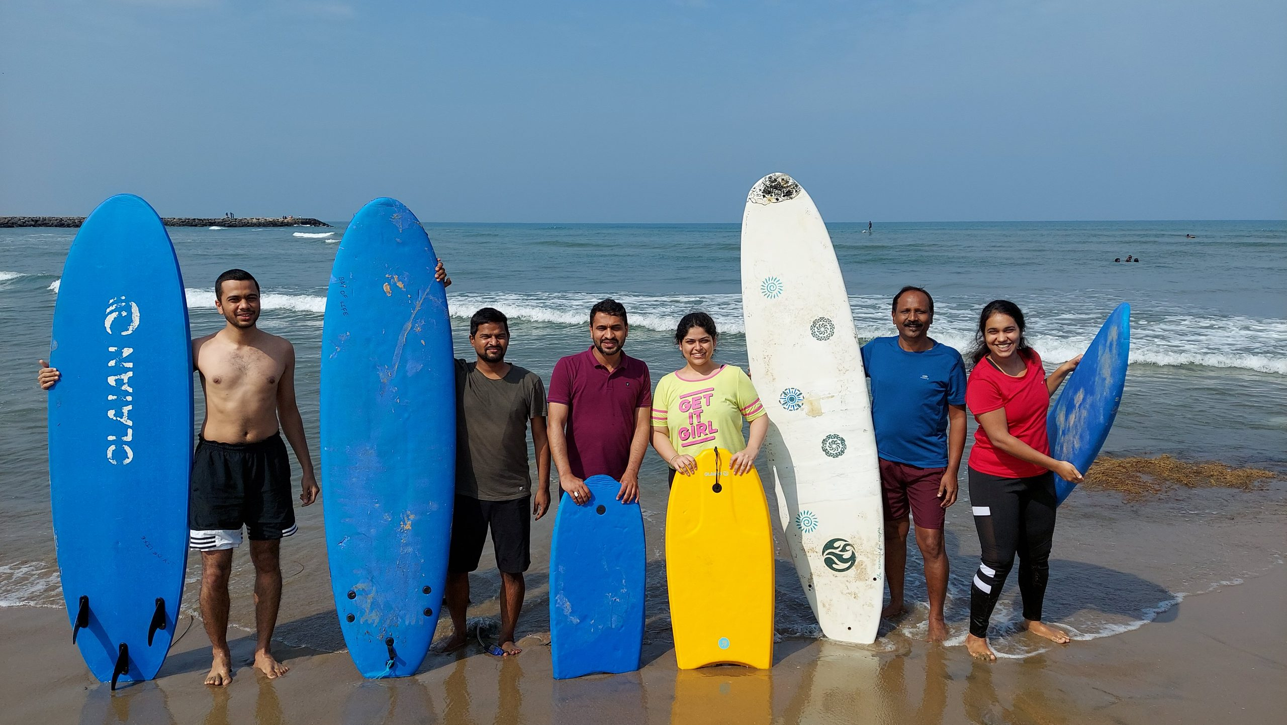 Students surfing the waves at Kovalam Beach